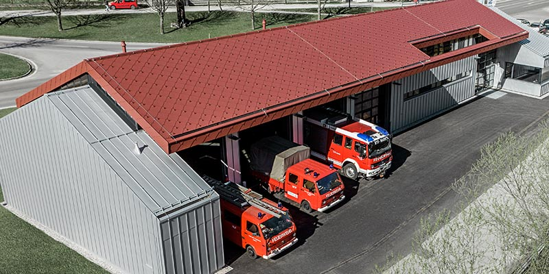 Fire station at the PREFA headquarters in Marktl, Austria, with a roof covered in red rhomboid roof tiles, and a standing seam roof and façade in metallic silver. Find more information about fire ratings here.
