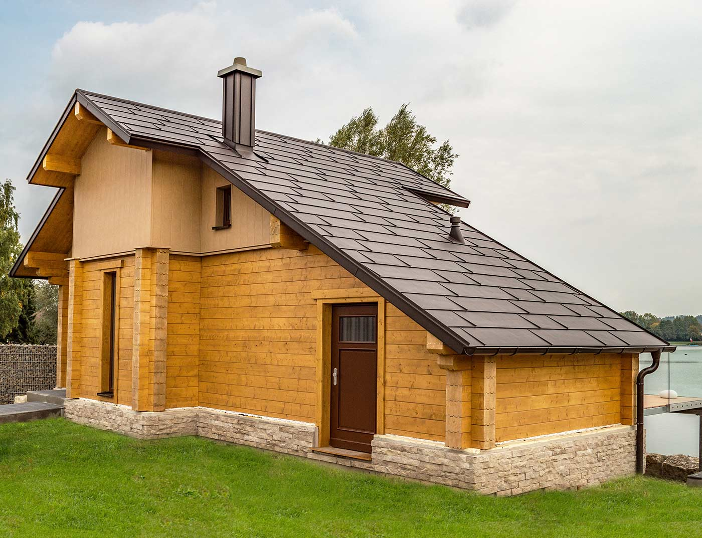 Lakeside house with PREFA FX.12 roof panels in nut brown and façade cladding in sand brown and wood.