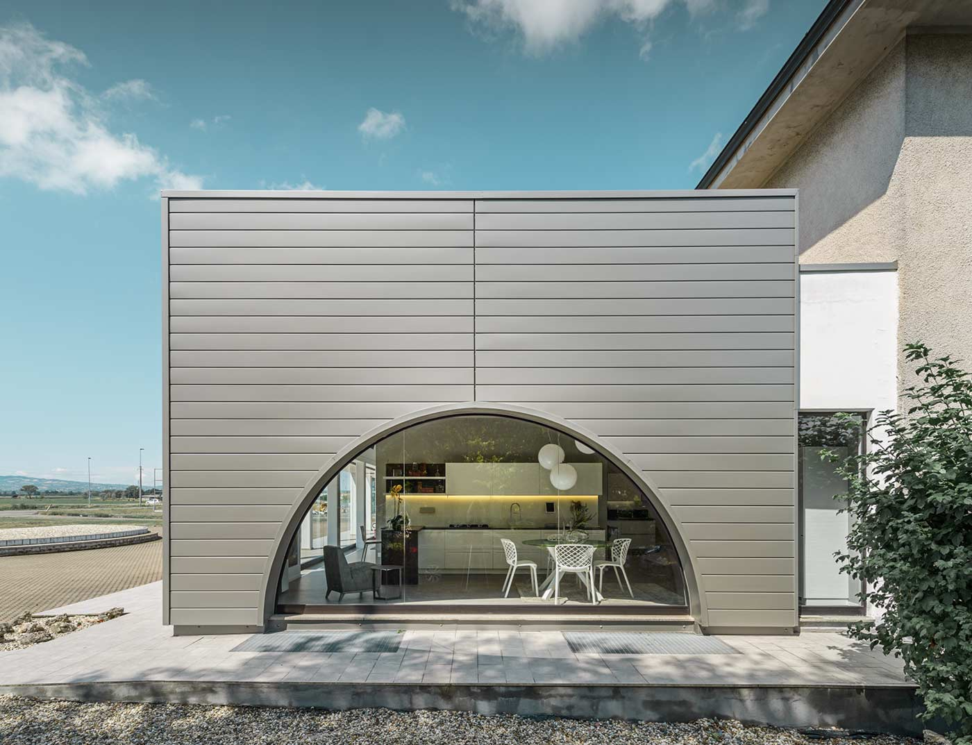 Flat-roof extension with a curved window façade, the façade is clad with horizontal aluminium panels, the PREFA sidings in smoke silver.