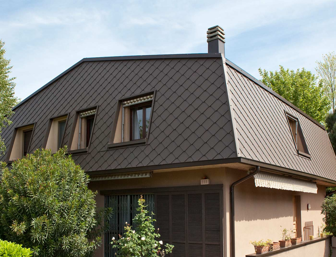 Mansard roof covered with PREFA 29 × 29 rhomboid wall tiles in brown. The upper part of the building was clad with a combination of horizontal larch wood panels and PREFA Siding.X aluminium panels in anthracite.