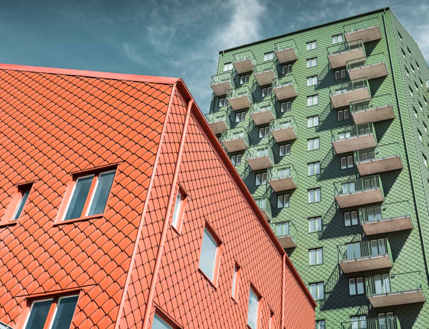 Swedish residential buildings with balconies and PREFA rhomboid wall tiles in green and brick red.